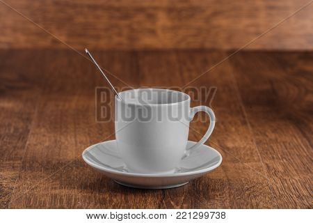 white coffe Cup with spoon on white saucer on dark brown wooden background. morning concept