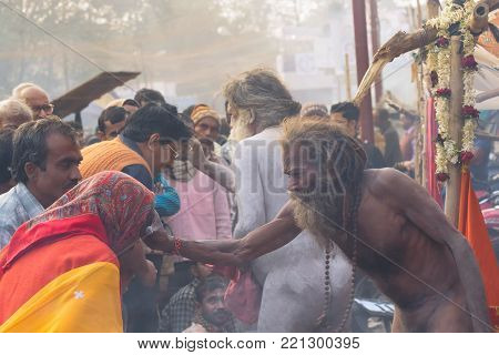 BABUGHAT, KOLKATA, WEST BENGAL / INDIA - 11TH JANUARY 2015 : Hindu Sadhu with white ash applied on body and face, blessing sari clad Indian devotee woman.