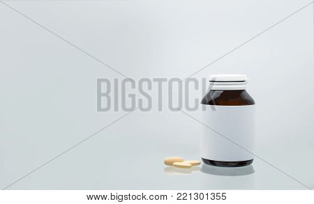 Three tablets of vitamin C 1,000 mg on white background and amber bottle with blank label and copy space for text. Vitamin and supplement concept. Antioxidant