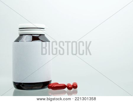 Macro shot of red multivitamins capsule pills for pregnant woman with amber bottle and blank label and copy space isolated on white background. Vitamin and supplement for pregnancy and elderly people.