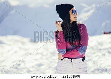 young and stylish brunette in the snowy mountains