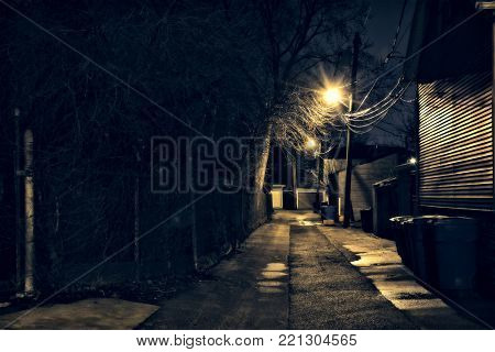 Dark, gritty and wet Chicago alley at night after rain.