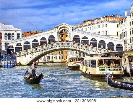 VENICE, iTALY - SEPTEMBER 21, 2017 Colorful Rialto Bridge Public Ferries Vaporetto Ferry Docks Gondola Touirists Grand Canal Venice Italy