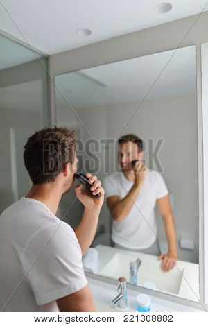 Man shaving using electric shaver trimming his beard in home bathroom- morning grooming routine people concept. Young man looking at mirror getting ready . Beauty facial care for men.