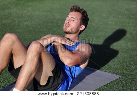 Fit man training at fitness gym doing situp crunches on exercise mat. Bodyweight floor exercises. Healthy and sport lifestyle. Man doing weight loss abs stomach exercise for ab muscles.