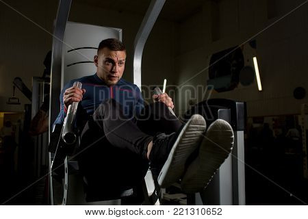 Young man making effort during difficult exercise for arms on sports equipment in gym