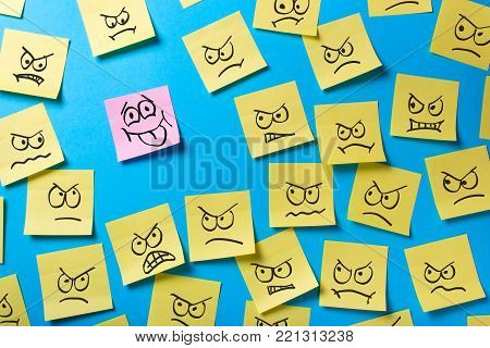 Unfinished tasks and goals. Office stickers with an angry face look at the smiling sticker that shows the language