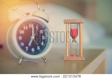 alarm clock with hourglass on the bed in bedroom.