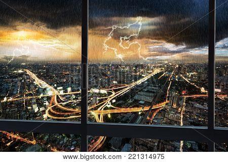 Night scene cityscape traffic with rain storm and thunderbolt lightning shoot from window internal building in Bangkok metropolis Thailand