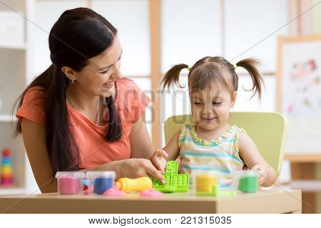 child kid girl and her mother play colorful clay toy at nursery or kindergarten