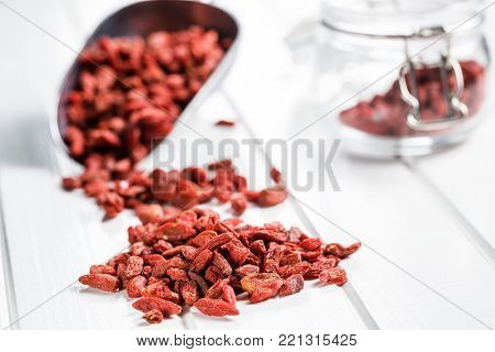 Dried goji berries on white table.