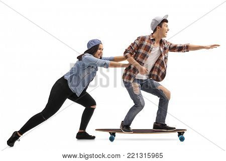 Full length profile shot of a teenage girl pushing a teenage boy on a longboard isolated on white background