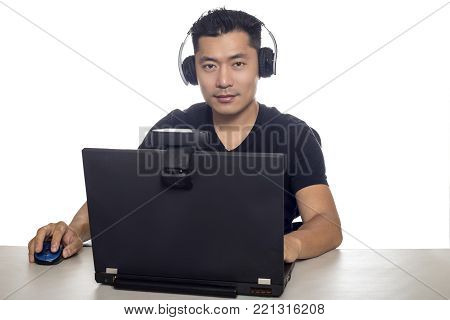 Asian male wearing headphones playing a video game and streaming online with a webcam on a laptop pc.  The image depicts entertainment industry and electronics competition or e-sports. poster