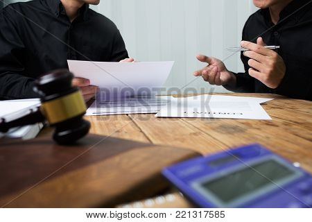 A team of lawyers and legal advisors working together. Discuss the details of the case of the accused.