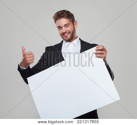 Young man in formal clothing holding blank paper and showing thumb up smiling at camera.