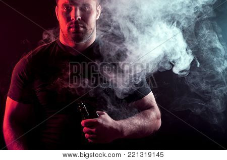 A young stylish male smoker in a black T-shirt exhales a large cloud of smoke from vape on a black isolated background