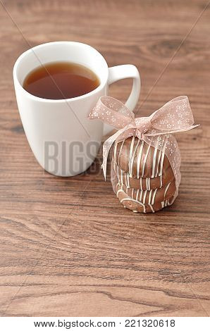 A stack of chocolate covered biscuits tied with a pink ribbon and a  white mug