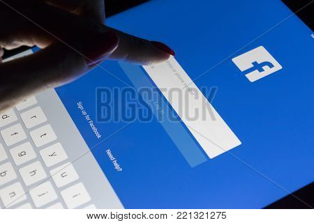Sankt-Petersburg, Russia, January 9, 2018: A woman's hand is touching screen on tablet Apple iPad Pro at night with Facebook homepage webpage.  Facebook the biggest social network website
