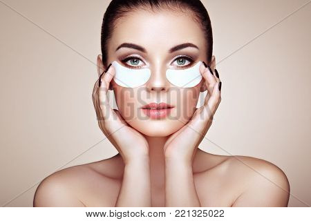 Portrait of Beauty Woman with eye Patches showing an effect of Perfect Skin. Beautiful Face of young Woman with clean Fresh Skin and bare shoulders on beige background. Brunette Spa Girl