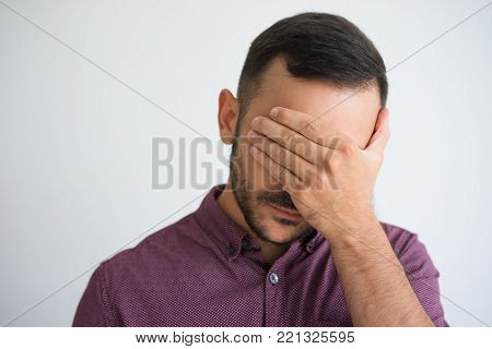 Closeup of young man covering eyes with hand. Depression concept. Isolated front view on grey background.
