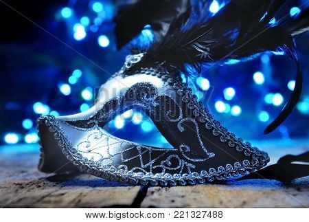 carnival mask with feather on blue lights background
