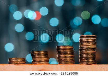 Money savings concept with coin stack and increasing columns of metal currency
