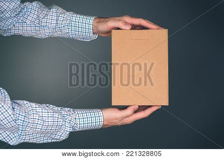 Man holding cardboard box package for mock up design. Courier delivers packed object. poster