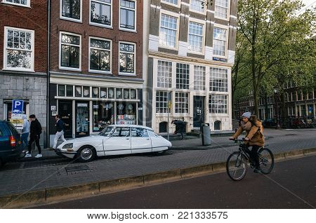 Amsterdam, Netherlands - 25 April, 2017: Adult woman rides a bicycle against parked vintage Citroen DS in historical part of Amsterdam with typical traditional houses.