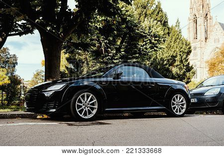 STRASBOURG, FRANCE - OCT 1, 2017: Modern luxurious Audi TT sport car parked in city with church building in the background