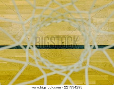 Look down through white string net, hardwood basketball board with black line. Basketball hoop in the sports hall.