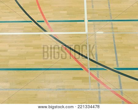 Painted wooden floor of sports hall with colorful marking lines. Schooll gym hall.