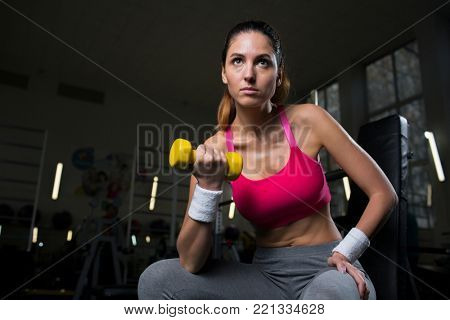Young female in activewear sitting in gym and exercising with dumbbells