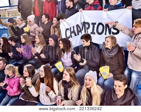 Fans cheering in stadium holding champion banner and singing on tribunes. Soccer game. People holding banner with Champion banner happily eating popcorn.