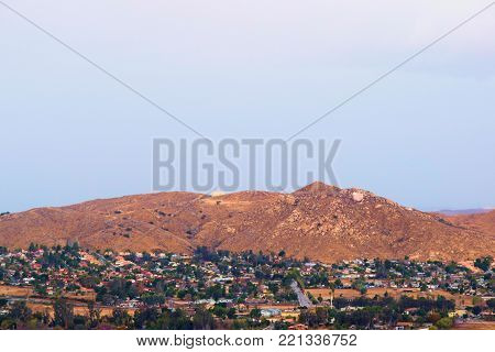 Urban sprawl beside barren hills with storm clouds above taken in Riverside, CA