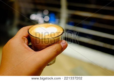 In selective focus of a female hand holding a small glass of hot latte with heart sign latte art on top and blur balcony at night with bokeh ligh