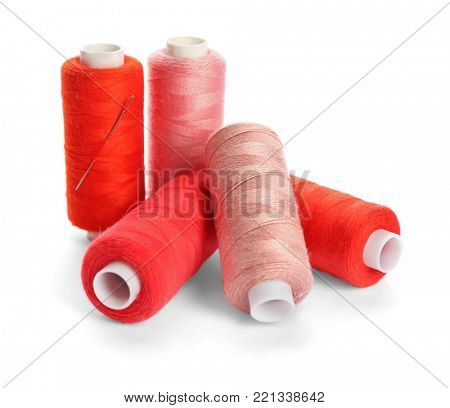 Red and pink threads of different shades on white background