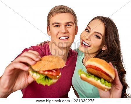 Couple eating fast food. Man and woman eat hamburger with ham. Friends holding two burder junk on white background isolated. Loving couple prefers fast food to homemade dinner. Discounts for fast food