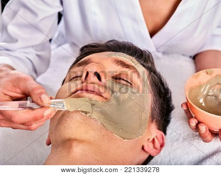 Mud facial mask of woman in spa salon. Massage with clay full face. Girl on with therapy room. Female lying wooden spa bed. Removing black dots. Anti-aging cosmetic mask.