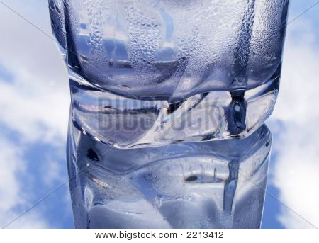 poster of Weeping glass of water with drops on background with blue sky and clouds
