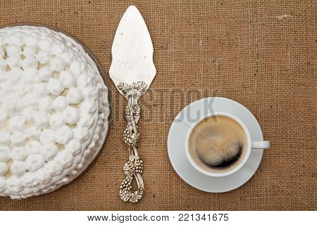 Biscuit cake decorated with whipped cream, silver cake lifter and cup of coffee on table with sackcloth. Top view