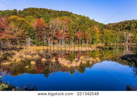 Concept of ecological tourism. Magnificent resort Mont Tremblant. The pond is smooth like a mirror. Foliage of autumn forests is reflected in pond