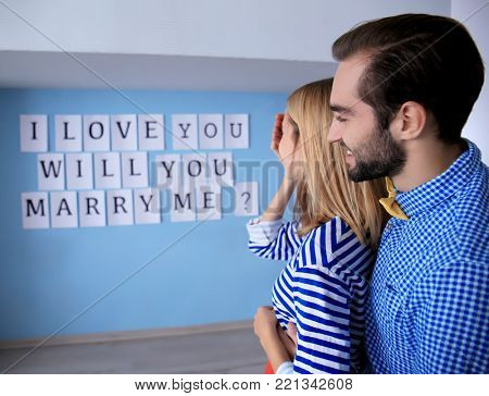 Marriage proposal on wall as surprise made by young man for his beloved girlfriend on engagement day