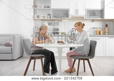 Senior woman and caregiver drinking tea at home