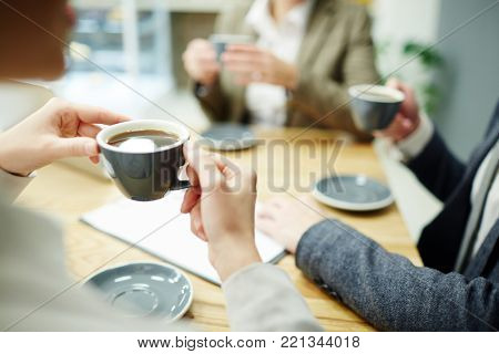 Cup of black tea or coffee held by businesswoman during coffee-break with colleagues