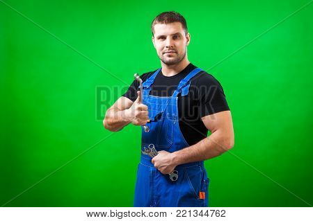 A young male construction worker wearing a black T-shirt and a blue construction jumpsuit is having fun and holding a tape rule  like a rapier on a green isolated background