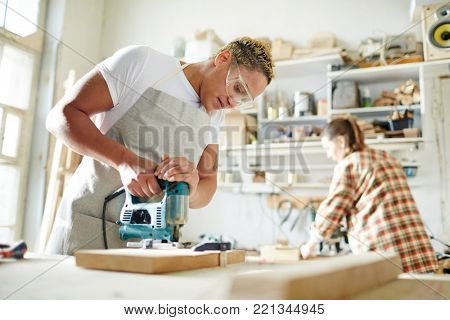 Carpenter in protective eyeglasses sawing wood with electric handtool in workshop