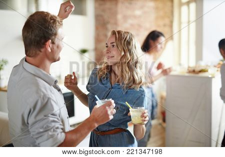 Young amorous couple with drinks dancing at home party with their friends on background
