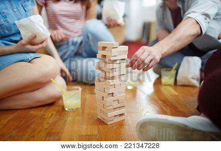 Tower of wooden bricks on the floor and several friends around it during play