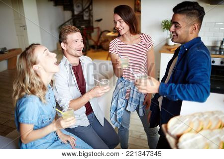 Cheerful friends with drinks talking and having fun while gathering at home