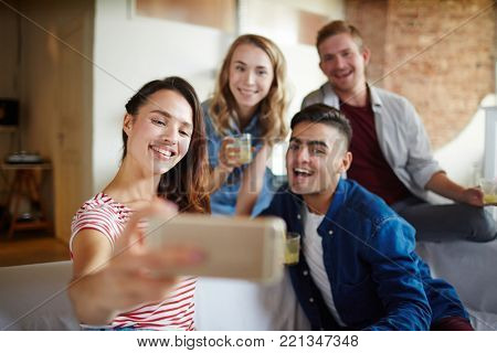 Young woman with smartphone making selfie with her friends at home